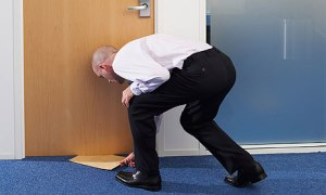 Businessman Passing Envelope Under Office Door